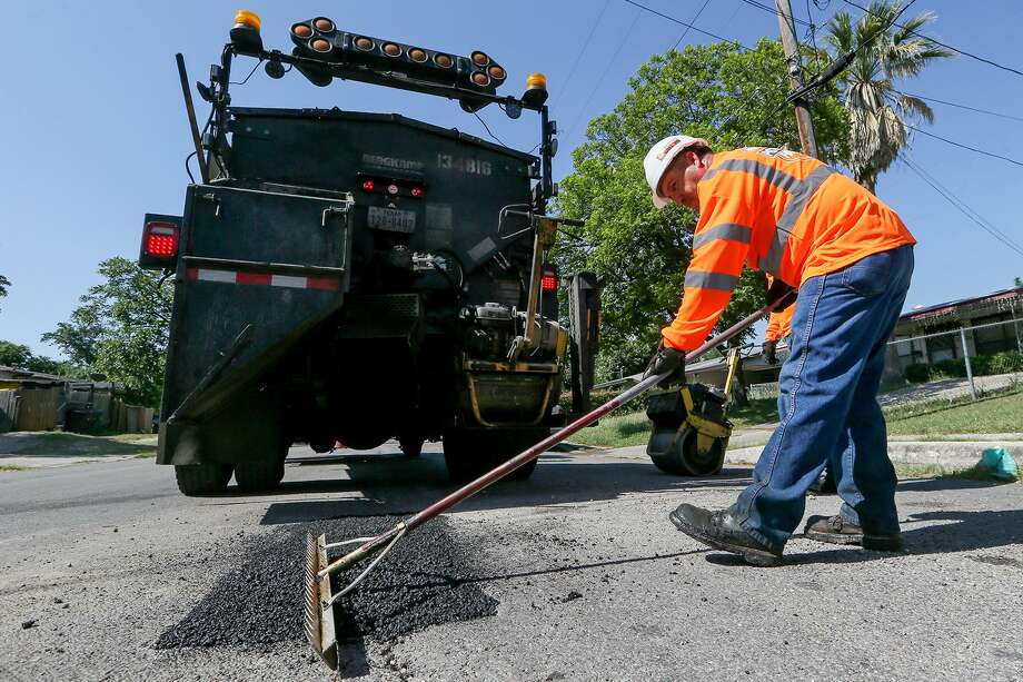 Jesse Cisneros with the city's Transportation and Capital Improvements (TCI)  levels hot asphalt with a rake before rolling it while reapiring a pothole on Yolanda St. on the city's West Side on Wednesday, May 16, 2018.  MARVIN PFEIFFER/mpfeiffer@express-news.net Photo: Marvin Pfeiffer, Staff / San Antonio Express-News / Express-News 2018