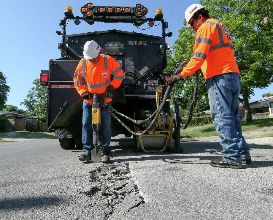 Jesse Cisneros (left) and Ramiro Sanchez with the city's Transportation and Capital Improvements work to repair a pothole on Yolanda Street last year. The TCI crews repaired a record 100,000 potholes for the 2019 fiscal year. MARVIN PFEIFFER/mpfeiffer@express-news.net Photo: Marvin Pfeiffer /San Antonio Express-News / Express-News 2018