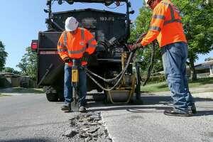 Jesse Cisneros (left) and Ramiro Sanchez with the city's Transportation and Capital Improvements work to repair a pothole on Yolanda Street last year. The TCI crews repaired a record 100,000 potholes for the 2019 fiscal year. MARVIN PFEIFFER/mpfeiffer@express-news.net