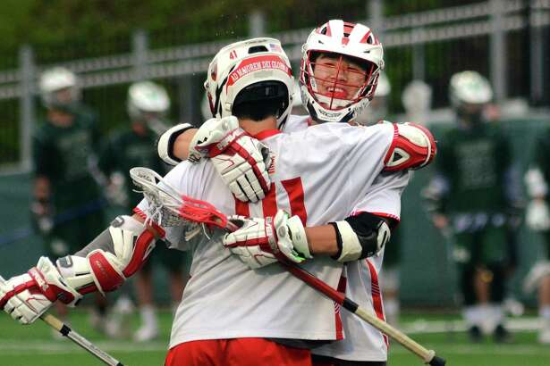Fairfield Prep's Jae Young Stuhlman (42), facing camera, hugs teammate Ethan Grandolfo (41), after Grandolfo scored a goal against Guilford during boys lacrosse action in Fairfield, Conn., on Tuesday May 22, 2018.