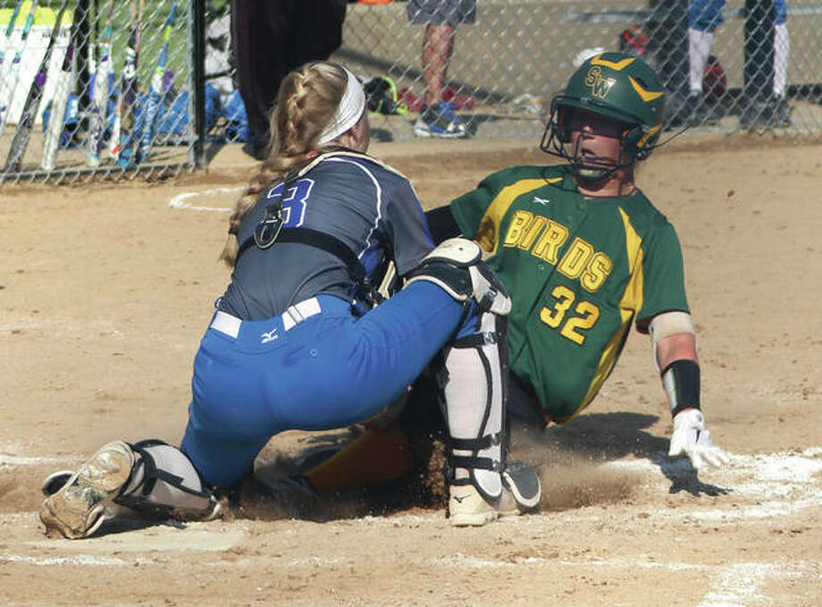 Marquette Catholic catcher Jada Johnson (left) tags out Southwestern's Bri Roloff at the plate to keep the game scoreless in the fourth inning Tuesday in the championship game of the Marquette Class 2A Regional at Moore Park in Alton. Photo:     Greg Shashack / The Telegraph