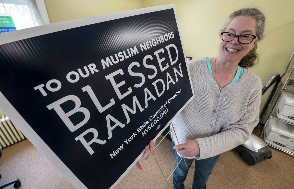 """Administrative assistant Laura Wayman of Capital Area Council of Churches holds """"Blessed Ramadan"""" sign in her office Tuesday May 22, 2018 in Albany, N.Y. (Skip Dickstein/Times Union)"""