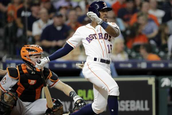Houston Astros' Tony Kemp (18) hits a two-run single in front of San Francisco Giants catcher Buster Posey during the fourth inning of a baseball game Tuesday, May 22, 2018, in Houston. (AP Photo/David J. Phillip)