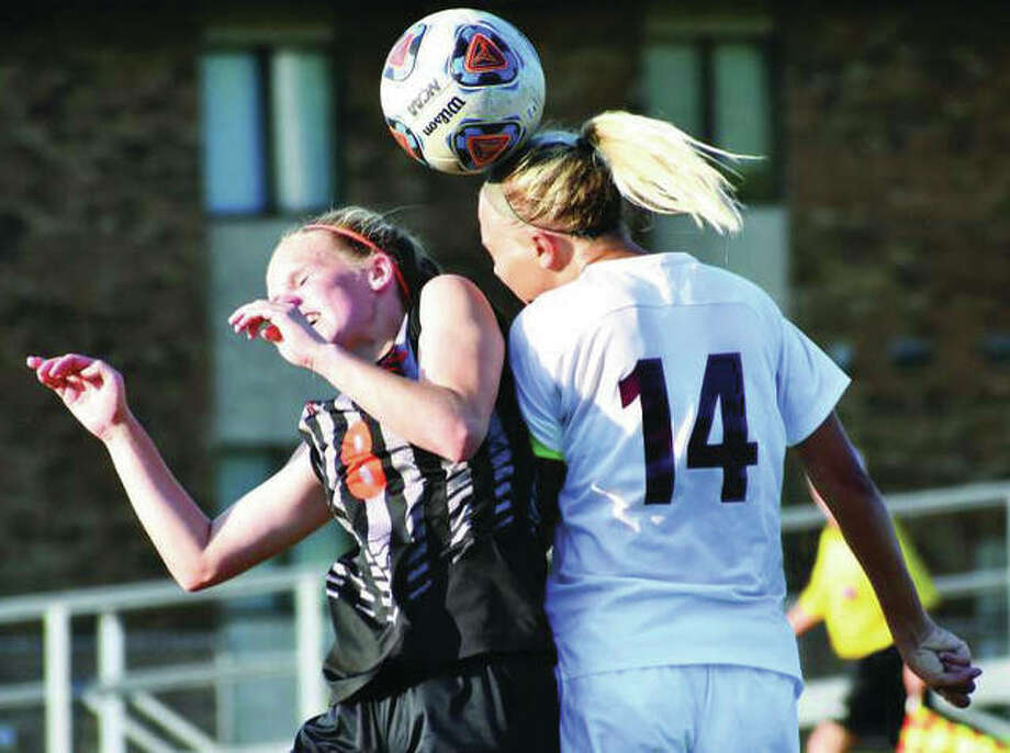 Edwardsville defender Sarah Kraus (left) goes up for a 50-50 ball against Belleville West's Taylor Mathenia during first-half action in a Class 3A sectional semifinal gamea at McKendree's Leemon Field on Tuesday in Lebanon. Photo:     Matthew Kamp / Hearst Newspapers