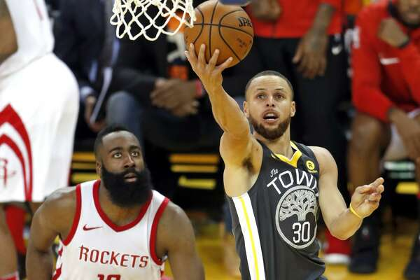 Golden State Warriors' Stephen Curry scores past Houston Rockets' James Harden in 3rd quarter during Game 4 of NBA Western Conference Finals at Oracle Arena in Oakland, CA on Tuesday, May 22, 2018.