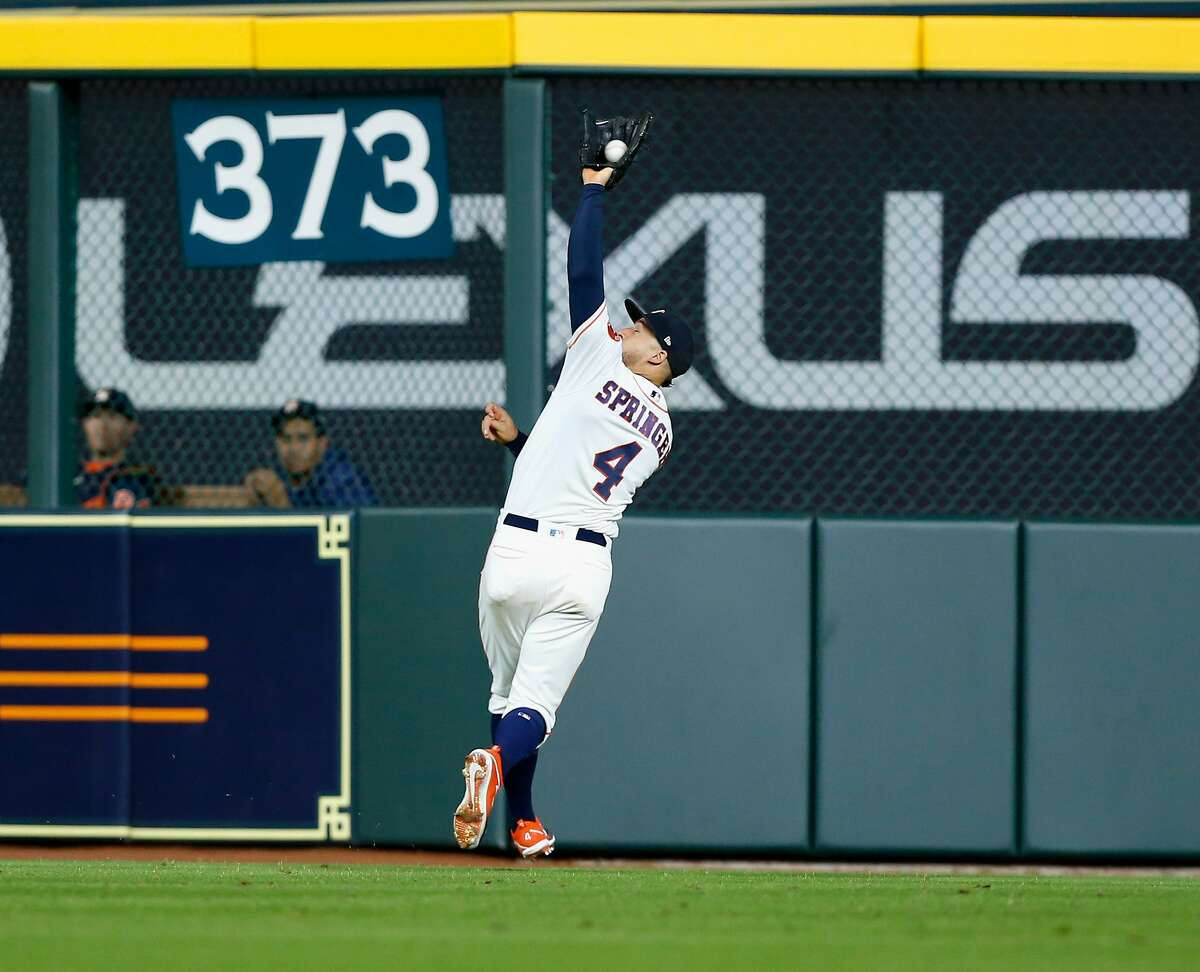 HOUSTON, TX - MAY 22: George Springer #4 of the Houston Astros makes an over the shoulder catch in the eighth inning on a ball hit by Evan Longoria #10 of the San Francisco Giants at Minute Maid Park on May 22, 2018 in Houston, Texas. (Photo by Bob Levey/Getty Images)