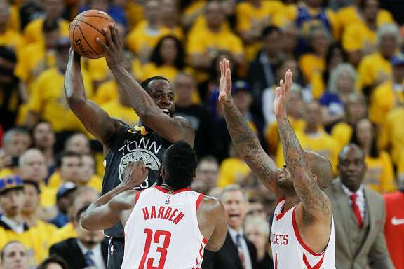 Golden State Warriors' Draymond Green passes off over Houston Rockets' James Harden and PJ Tucker in the fourth quarter during game 4 of the Western Conference Finals between the Golden State Warriors and the Houston Rockets at Oracle Arena on Tuesday, May 22, 2018 in Oakland, Calif.
