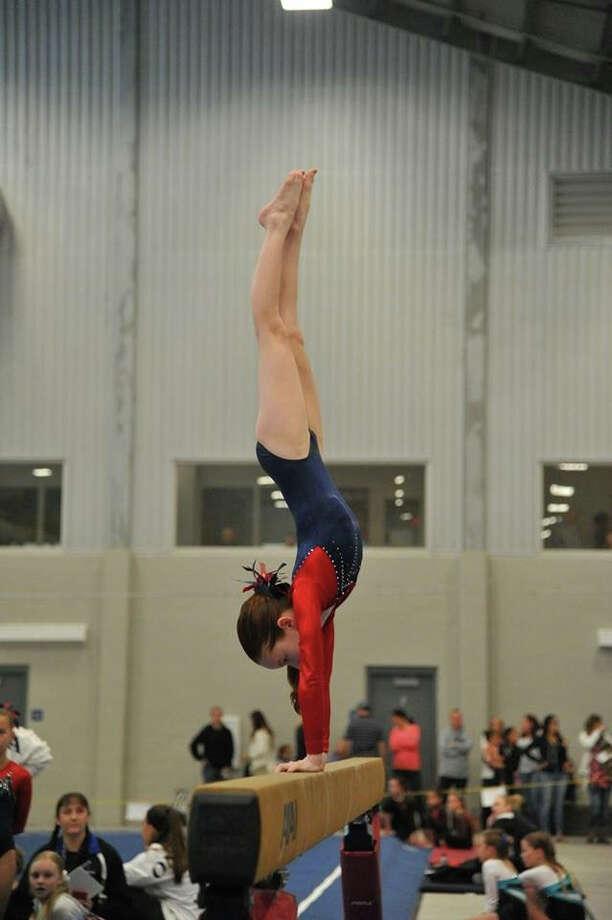 Darien 4 gymnast Madeleine McGivney scored 9.25 for her beam routine at the YMCA Northeast Regional Championship meet in Maine. Photo: Contributed Photo / Darien News contributed