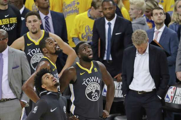 Golden State Warriors' Draymond Green, Quinn Cook, Kevin Durant, Klay Thompson and head coach Steve Kerr watch video review with 0.5 seconds remaining in Houston Rockets' 95-92 win in Game 4 of NBA Western Conference Finals at Oracle Arena in Oakland, CA on Tuesday, May 22, 2018.
