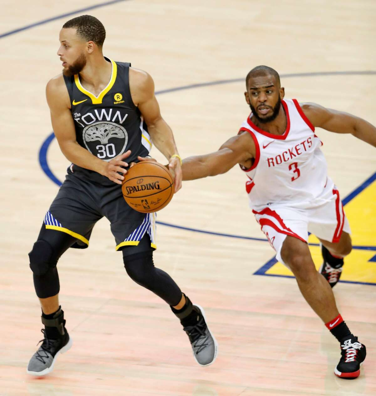 Houston Rockets' Chris Paul tries to steal the ball from Stephen Curry in 2nd quarter of Houston's 95-92 win during Game 4 of NBA Western Conference Finals at Oracle Arena in Oakland, CA on Tuesday, May 22, 2018.