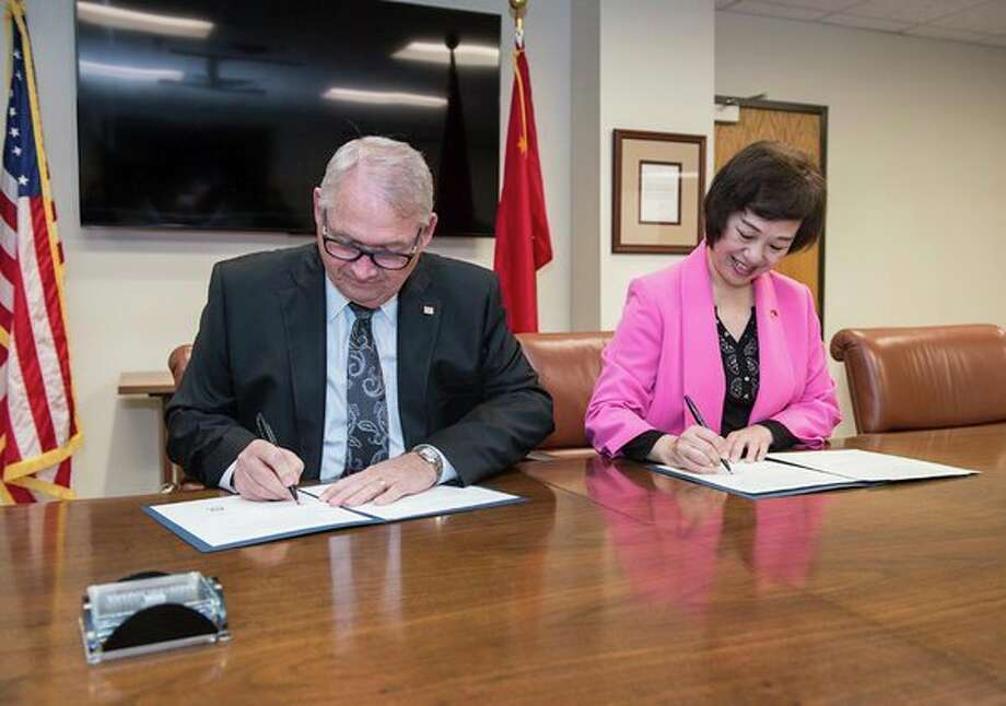 Donald Bachand, president of Saginaw Valley State University, and Chen Weiju, dean of nursing at Jinan University, sign a Memorandum of Understanding during a signing ceremony May 15 at SVSU. (Photo provided/SVSU)