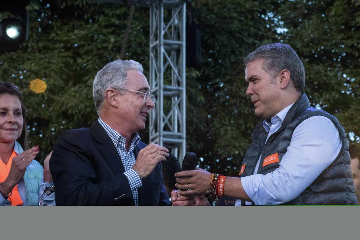 Alvaro Uribe (left), former president of Colombia, hands a microphone to Ivan Duque, presidential candidate for the Democratic Center Party, during the closing campaign rally in Bogota, Colombia, on May 20, 2018.