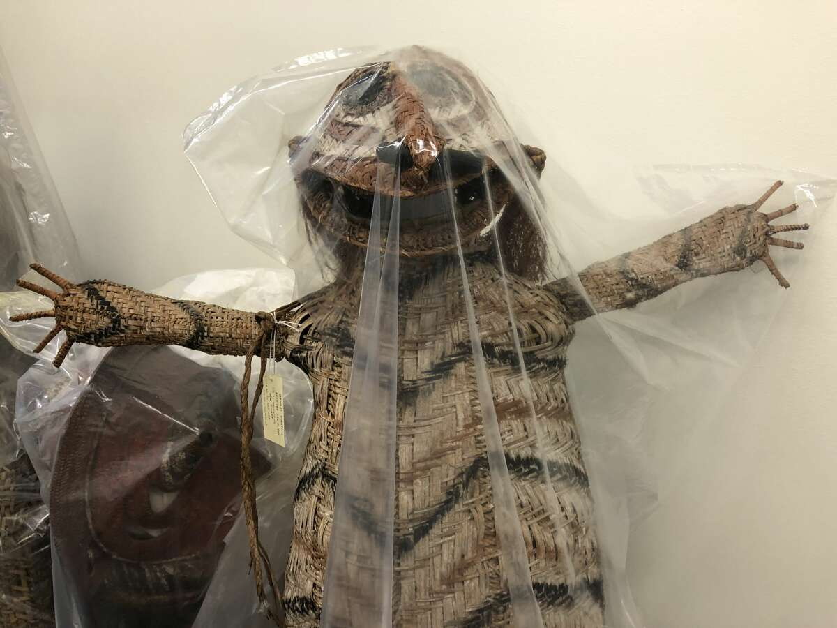 A piece of folklore from ancient New Guinea sits waiting for display in a dark closet.