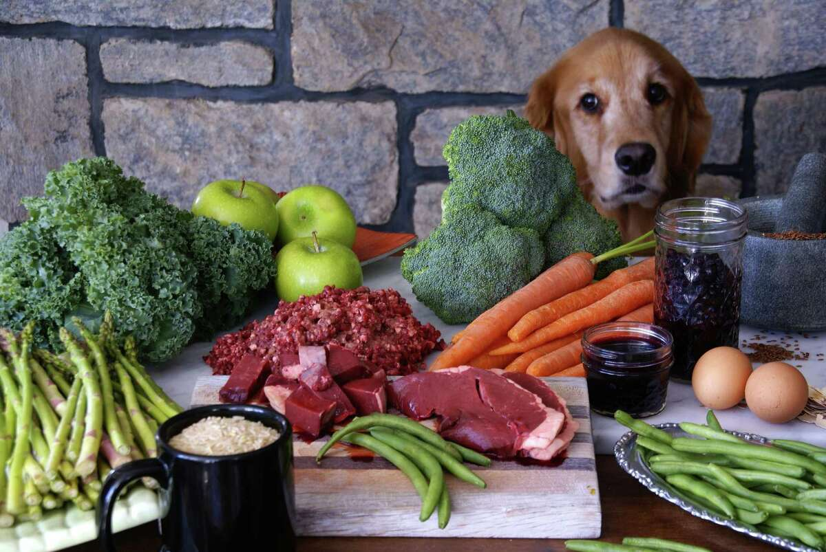 Hunter poses with some of the fresh vegetables and meats used to make Paul's Custom Pet Food.