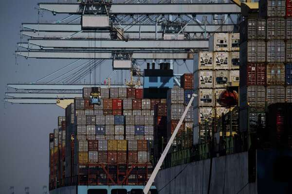 Gantry cranes stand over container ships at the Port of Los Angeles in Los Angeles on March 28, 2018.