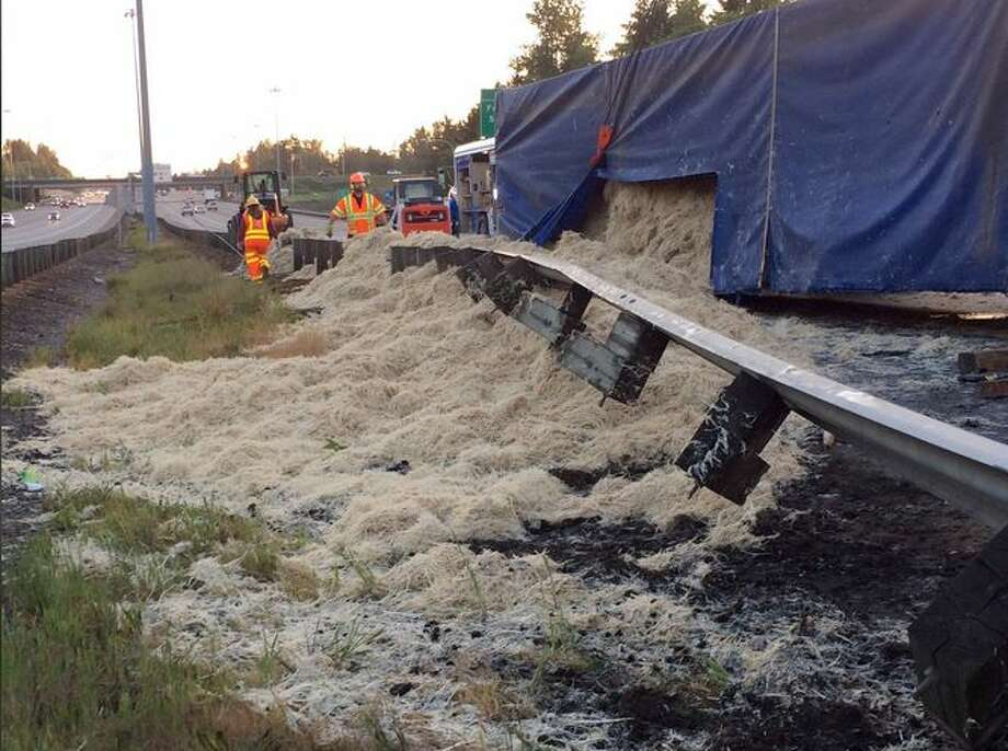 A semi truck that flipped on its side on northbound Interstate 5 in  Federal Way early Wednesday morning spilled 40,000 pounds of feathers on  the roadway, blocking nearly all lanes of traffic. Photo: KOMO