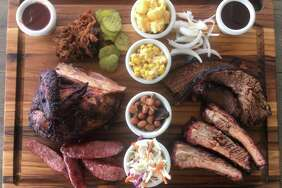 The barbecue board at True Texas BBQ includes (clockwise from top left) pulled pork, mac and cheese, creamed corn, brisket, pork ribs, coleslaw, brisket beans, sausage and a white meat chicken breast quarter.