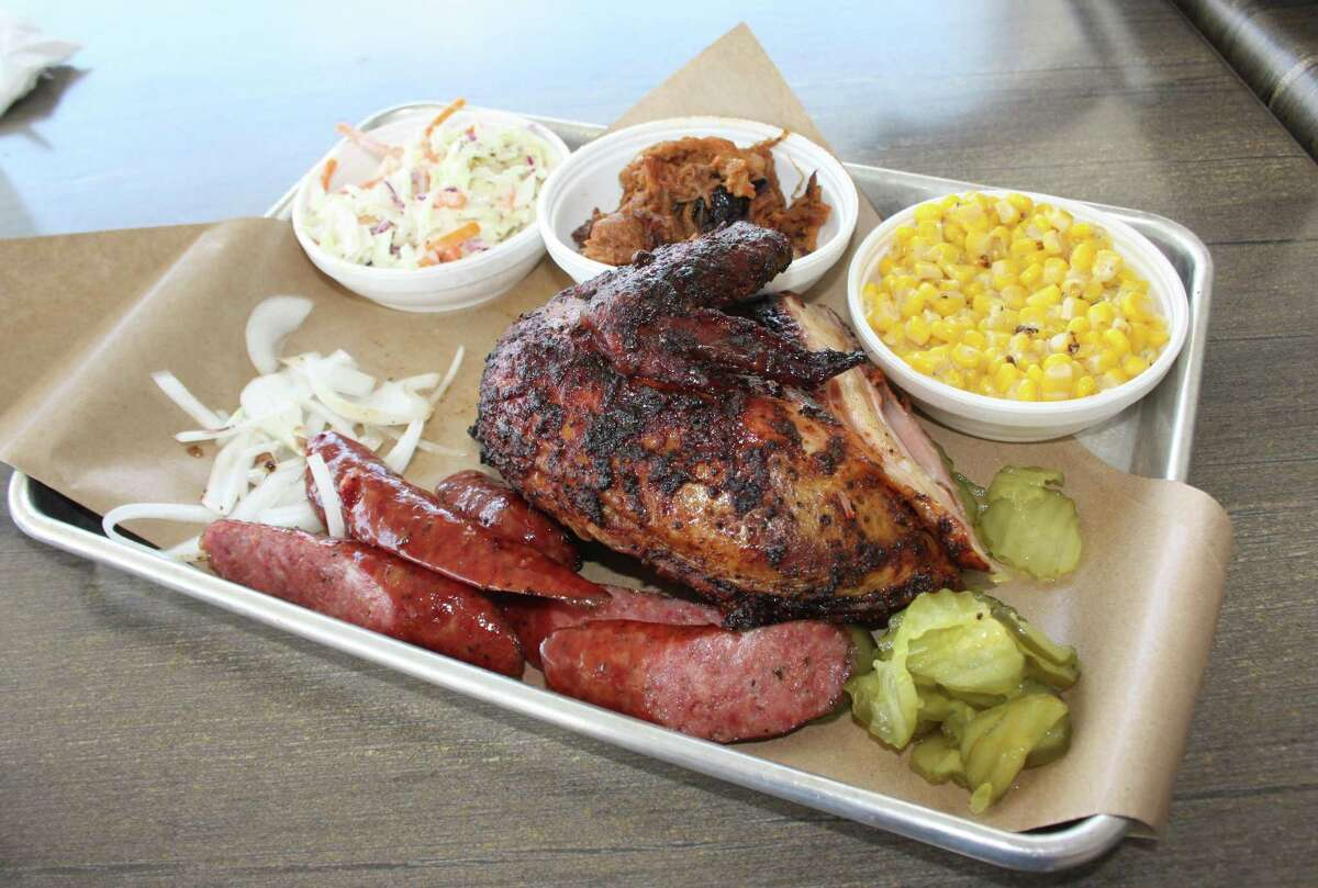 The three-meat plate ($14.79) comes with two sides. Pictured are sausage, pulled pork (middle dish) and a white meat breast quarter with coleslaw and creamed corn.