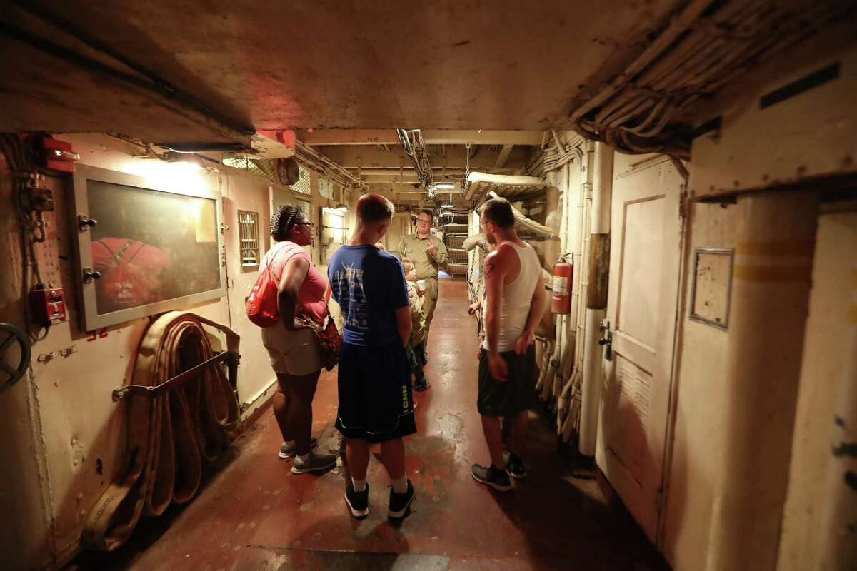 James Lightbody leads Cub Scouts and their parents on a tour of the Battleship Texas.