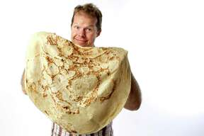 Express-News food writer Paul Stephen displays a piece of Lebanese mountain bread from Ali Baba International Market.