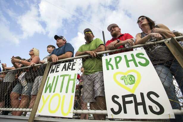 Baseball fans watch a Class 5A Region III playoff baseball game between Santa Fe and Kingwood Park above a pair of signs supporting the victims of the Santa Fe school shooting on Saturday, May 19, 2018, in Deer Park. ( Brett Coomer / Houston Chronicle )