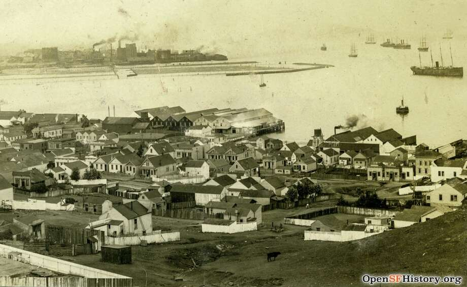 """BUTCHERTOWN Bordering streets: Evans/Selby/Islais Creek/SF Bay  In 1880s a group of butchers purchased 81 acres of waterlogged land in southeastern SF to establish a """"Butchers Reservation"""" for slaughtering animals. While Butchertown's heyday ended by 1906, slaughterhouses remained in the Bayview until 1971. FoundSF details Butchertown's history. Photo postcard view northeast from hill toward Islais Creek outlet. Fairfax Avenue, cottages, California Tallow Works, Chas. F. Lengeman shop. Courtesy of OpenSF"""