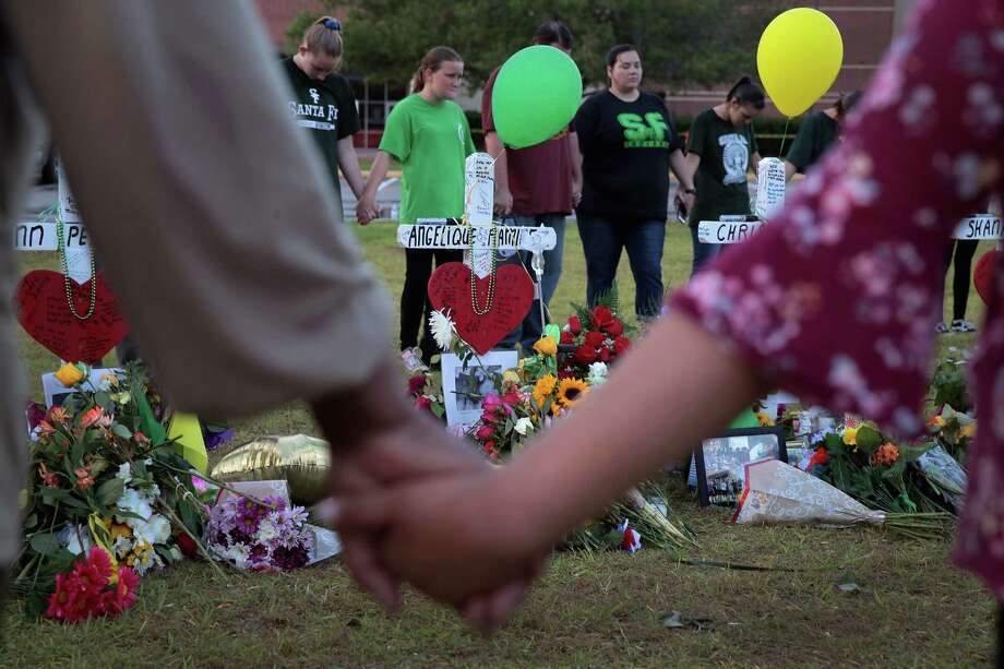 Mourners pray around a memorial in front of Santa Fe High School on May 21, 2018 in Santa Fe, Texas. Photo: Scott Olson, Getty Images / 2018 Getty Images