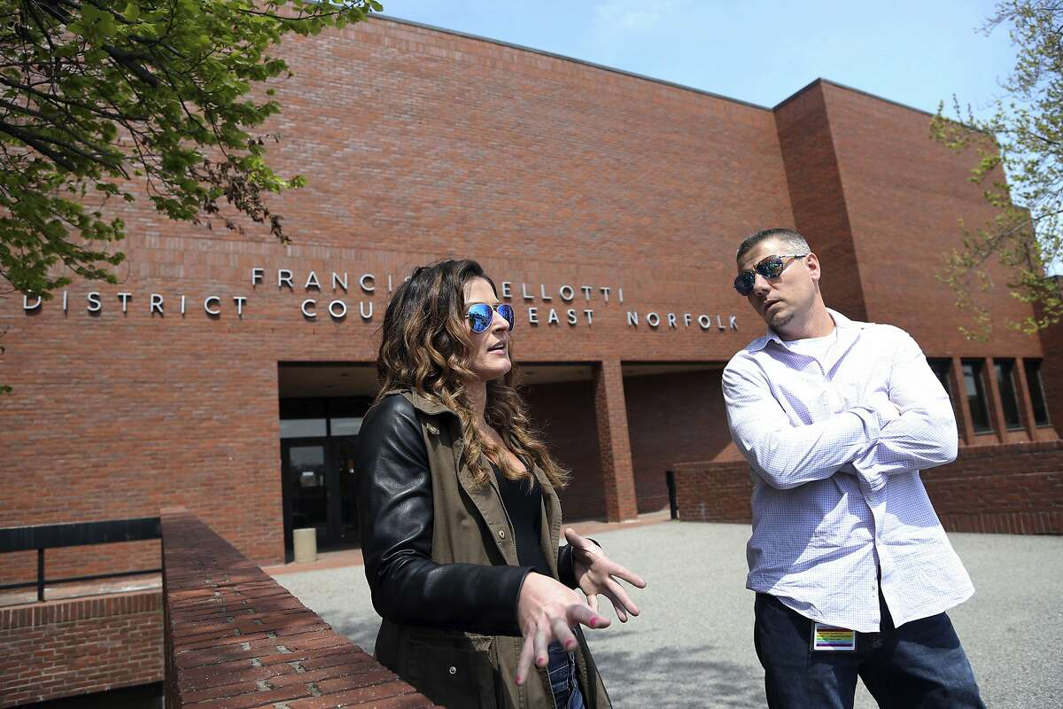 In this May 7, 2018 photo, Patrick Cronin, right, a director at the Northeast Addictions Treatment Center in Quincy, and Lizabeth Loud, 32, of Randolph, Mass., speak about their experiences of being involuntarily committed for substance abuse treatment, outside District Court in Quincy, Mass. Cronin credits his sobriety to his parents' decision to have him involuntarily committed for heroin use almost 15 years ago. Loud's mother sought a judge's order to have her committed against her will. Three years later, Loud said her month in state prison was the wake-up call she needed. (AP Photo/Elise Amendola)