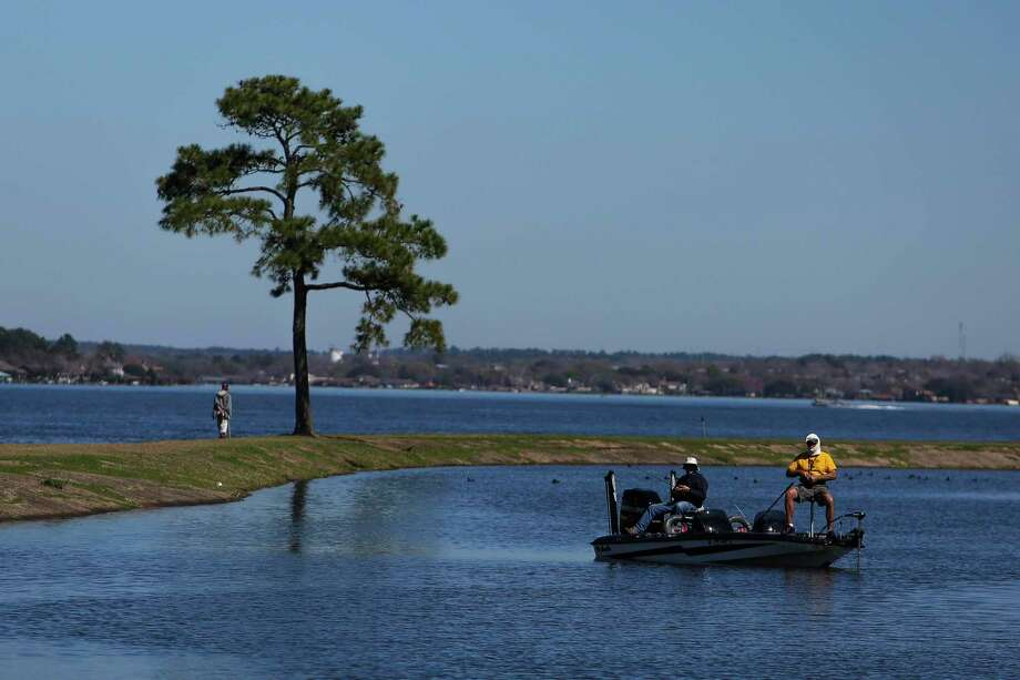 Men fish from their boat next to the Walden Yacht Club on Lake Conroe Wednesday, Feb. 22, 2017 in Montgomery. Photo: Michael Ciaglo, Staff / Houston Chronicle / Internal