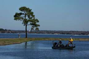 Men fish from their boat next to the Walden Yacht Club on Lake Conroe Wednesday, Feb. 22, 2017 in Montgomery. ( Michael Ciaglo / Houston Chronicle )