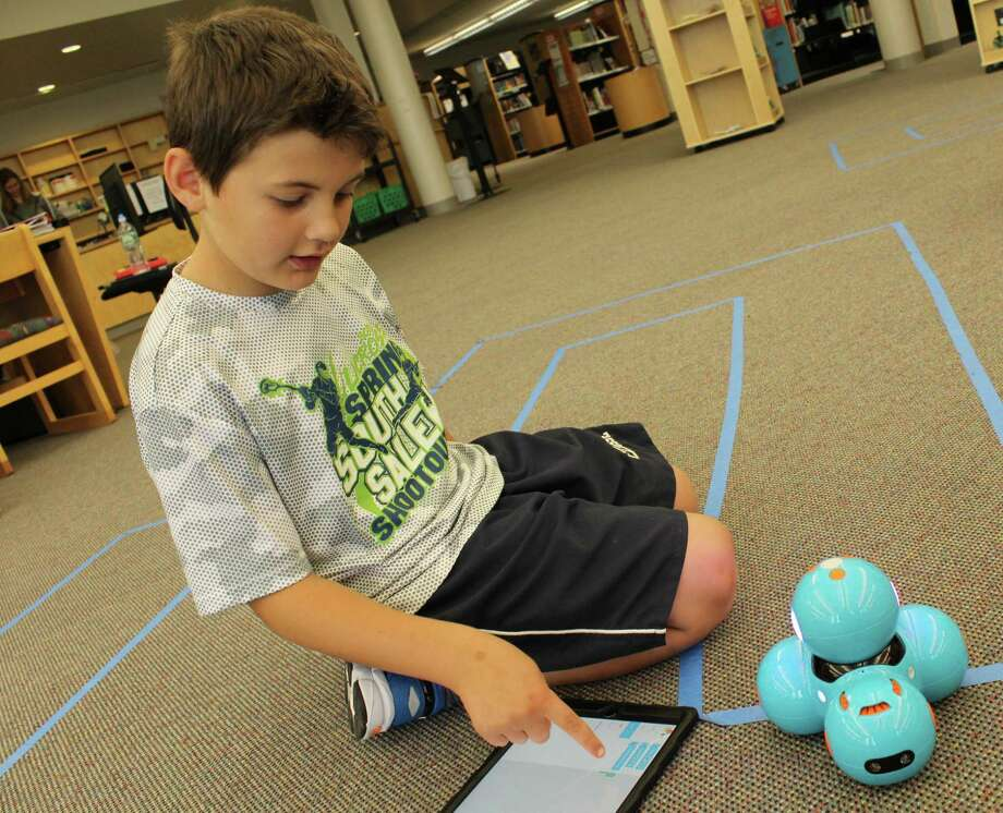 Cider Mill School third-grader William Viggiano, 9, programs instructions into his Dash and Go robot as a part of the new Ready Access Digital Learning program being implemented district-wide in Wilton public schools. Photo: Pat Tomlinson / Hearst Connecticut Media