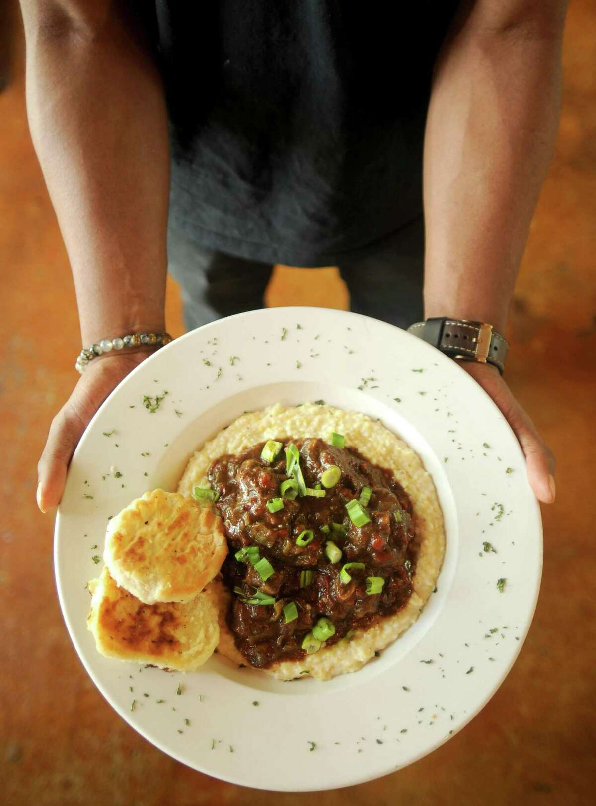 Gregory Adams, whose family opened The South Chicken & Waffles in late 2017, shows off the restaurant's braised oxtails and grits.