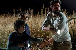 "This image released by Paramount Pictures shows Noah Jupe, from left, Millicent Simmonds and John Krasinski in a scene from ""A Quiet Place.""  Horror has emerged as one of the most bankable and inventive genres for a Hollywood desperate for hits. The $50 million debut of John Krasinksi's ""A Quiet Place"" suggests horror's big 2017 has carried over to 2018.(Jonny Cournoyer/Paramount Pictures via AP)"