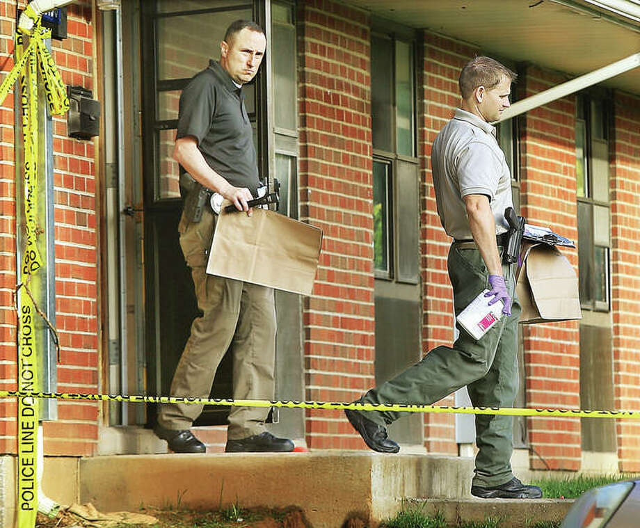 Alton Police evidence officer Michael Roderfeld, left, and an Illinois State Police crime scene investigator, right, walk out of the apartment Tuesday morning where two men were found shot late Monday night. A person of interest in the shootings was arrested and charged Wednesday. Photo:       John Badman | The Telegraph