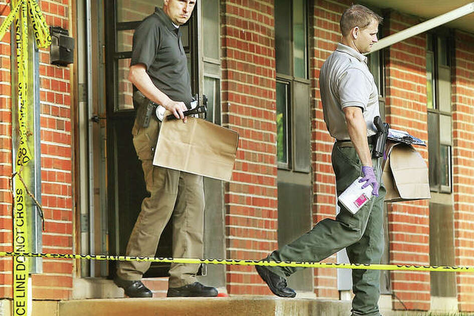 Alton Police evidence officer Michael Roderfeld, left, and an Illinois State Police crime scene investigator, right, walk out of the apartment Tuesday morning where two men were found shot late Monday night. A person of interest in the shootings was arrested and charged Wednesday.