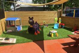 The kid-friendly play area at The Patio Southtown is covered with artificial turf.