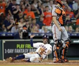 Houston Astros second baseman Jose Altuve (27) slides to score as San Francisco Giants catcher Nick Hundley (5) waits for the throw on the hit by Carlos Correa during the fifth inning of a baseball game Wednesday, May 23, 2018, in Houston. (AP Photo/Michael Wyke)