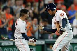 Houston Astros right fielder George Springer (4) celebrates with Jose Altuve after hitting a home run during the fifth inning of an MLB game at Minute Maid Park, Wednesday, May 23, 2018, in Houston.