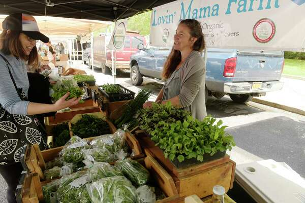 Corinne Hansch, right, who along with her husband owns and operates Lovin' Mama Farm out of Amsterdam, talks with customers under her tent at the Schenectady Greenmarket on Sunday, May 20, 2018, in Schenectady, N.Y.   (Paul Buckowski/Times Union)