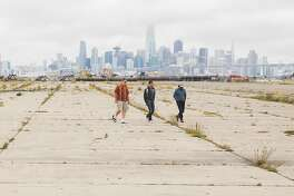 Three men walk across a large empty lot during the groundbreaking ceremony for the future site of Alameda Point Site A, a $1 billion waterfront development project at Alameda Point in Alameda, Calif. Wednesday, May 23, 2018.