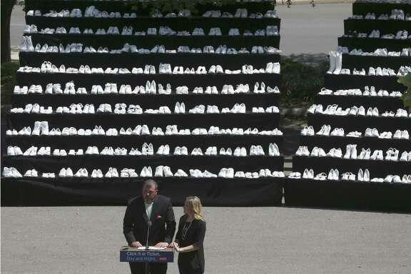 David and Wendy Mills talk in front of part of a display of 929 so-called ghost shoes May 8 at University Hospital about their daughter, Kailee, during the kick-off of the annual Click It or Ticket campaign encouraging people to wear seatbelts in cars. Kailee was killed in a car accident when she took her seatbelt off just 400 yards from her destination.
