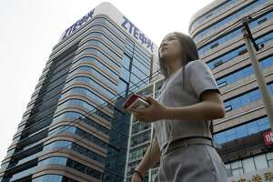 A woman passes by a ZTE building in Beijing, China recently. President Donald Trump's weekend social media musings about China injected new uncertainty into the Washington's punishment of Chinese tech giant ZTE and planned trade talks between the two countries.