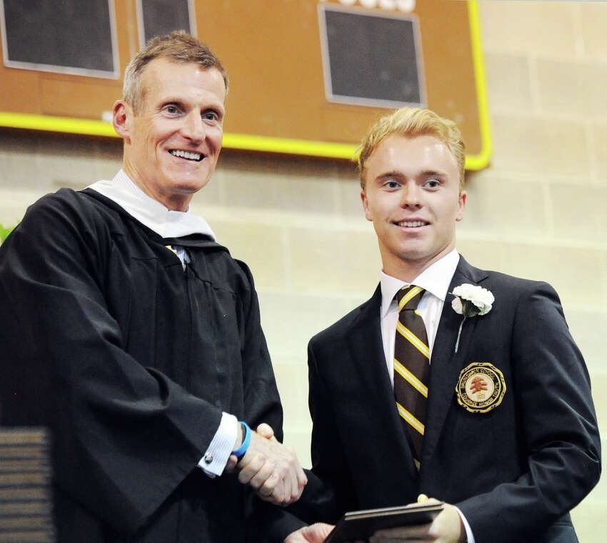 Brunswick School Headmaster Tom Philip, left, shakes hands with Charlie Berger, after handing Berger his diploma during the Brunswick School commencement in the Dann Gymnasium at the school in Greenwich, Conn., Wednesday, May 23, 2018. Berger said he will be attending Southern Methodist University in the fall and was one of Ninety-nine students that graduated from Brunswick.