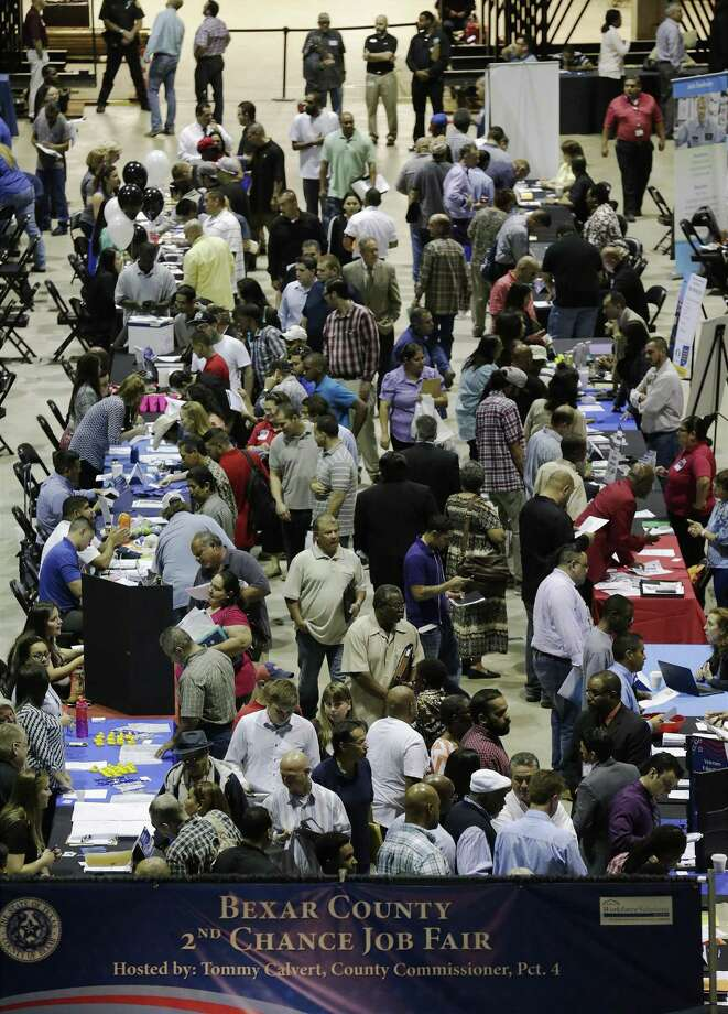 A crowd slowly make their way from table to table seeking jobs at the second chance job fair hosted by Bexar County Commissioner, Precinct 4 Tommy Calvert at the AT&T Center on Thursday, May 7, 2015. About 70 exhibitors were on site as some 1,800 applicants filled the arena seeking work. (Kin Man Hui/San Antonio Express-News) Photo: Kin Man Hui /San Antonio Express-News / ©2015 San Antonio Express-News