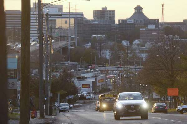 Traffic moves along East Main Street as the sun sets over the skyline of Stamford, Conn. Monday, Nov. 20, 2017.