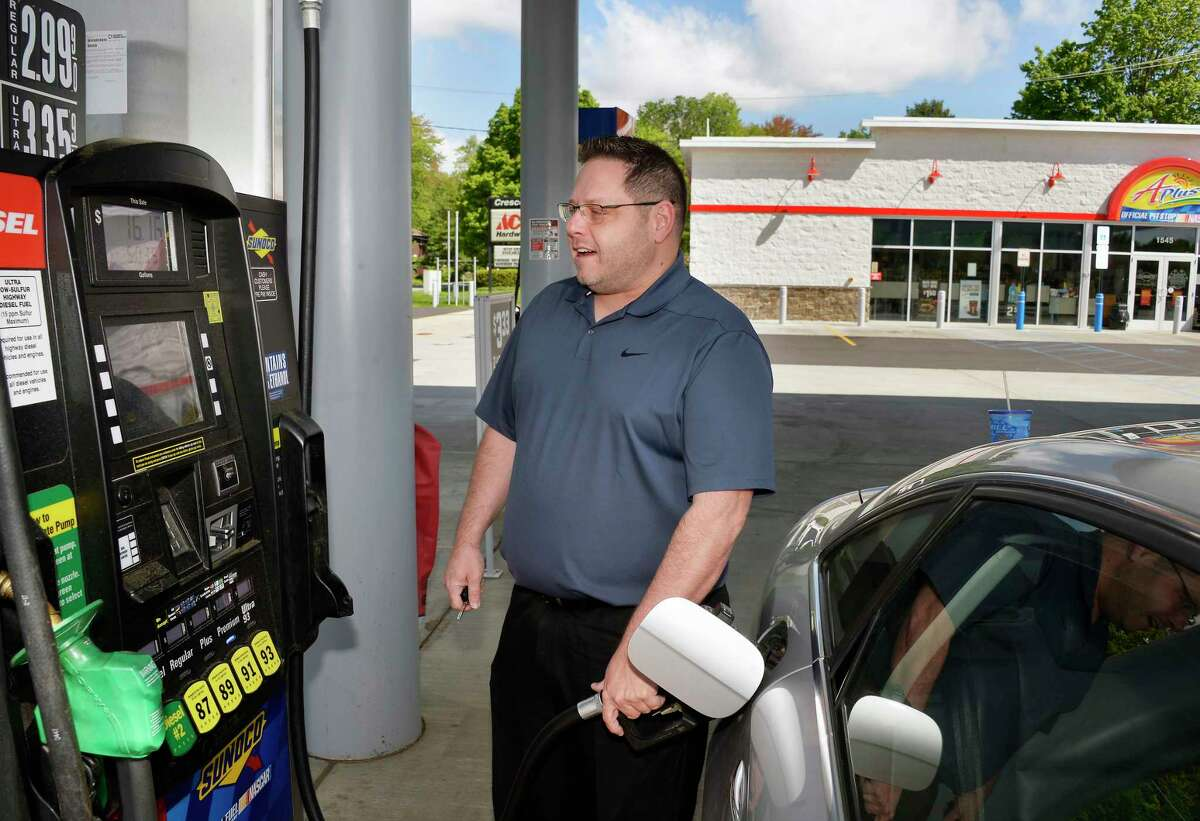 Dan Dmyszewicz pumps gas at the APlus Sunoco station off Northway Exit 8 Wednesday May 23, 2018 in Clifton Park, NY. Undaunted by rising gas prices, Dmyszewicz is planning a family road trip to North Carolina for the holiday. (John Carl D'Annibale/Times Union)