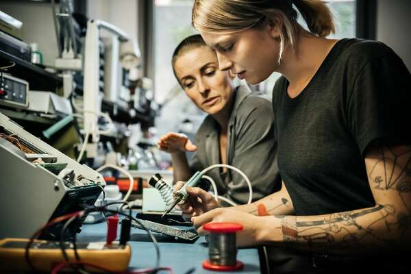 Female technician guiding a young female trainee in a workshop.