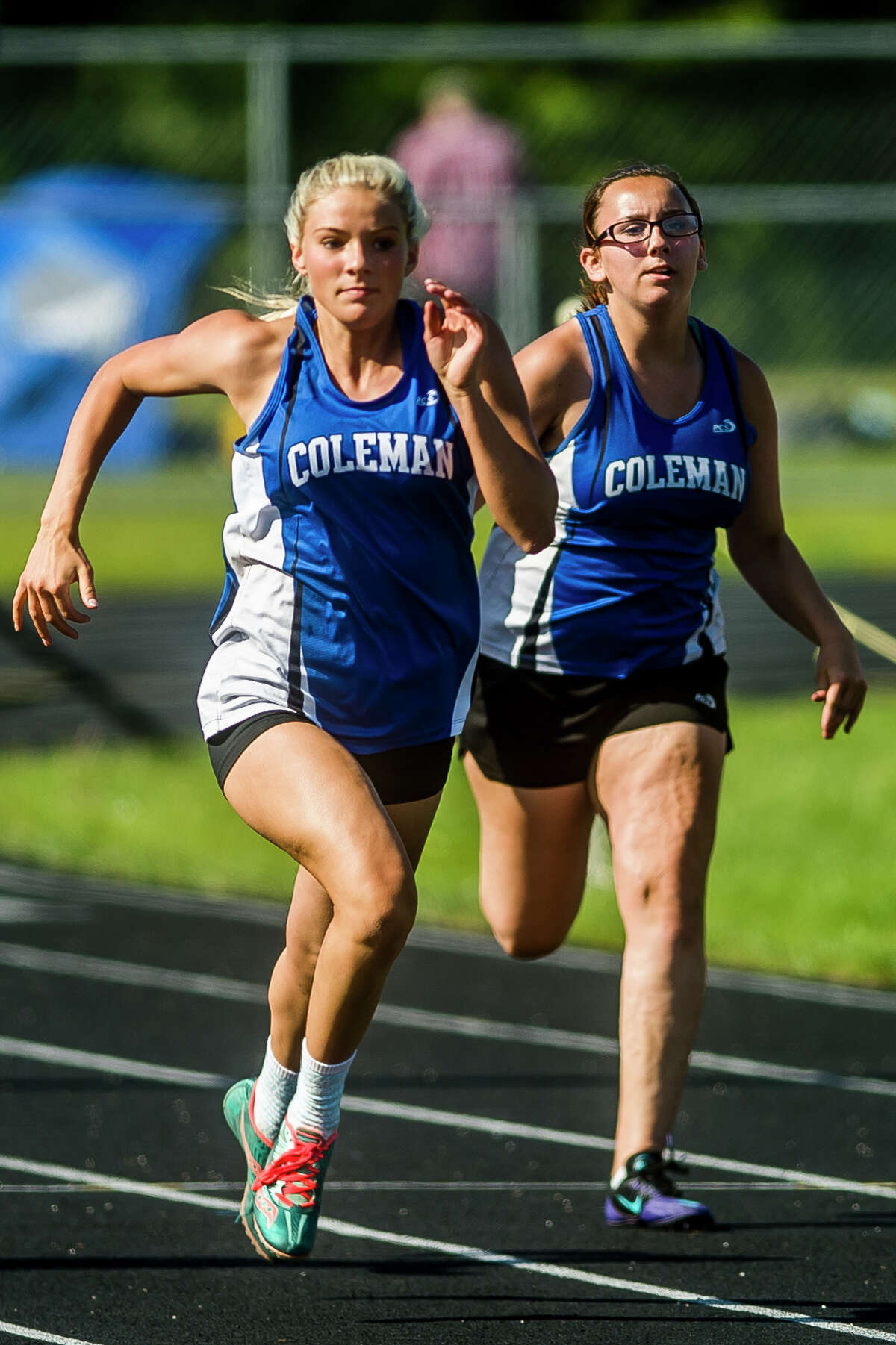 Coleman junior Makailyn Monson, left, and sophomore Brianna Guzman, right, compete in the 100-meter dash during a track and field meet on Wednesday, May 23, 2018 at Coleman High School. (Katy Kildee/kkildee@mdn.net)