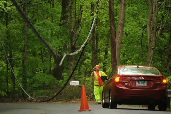 """A utility worker guides cars beneath low hanging power lines on Park Road in Oxford, Conn. on Tuesday, May 22, 2018. First Selectman George Temple called the May 15th storm that knocked out power to the town """"the worst natural disaster"""" in the town's history."""