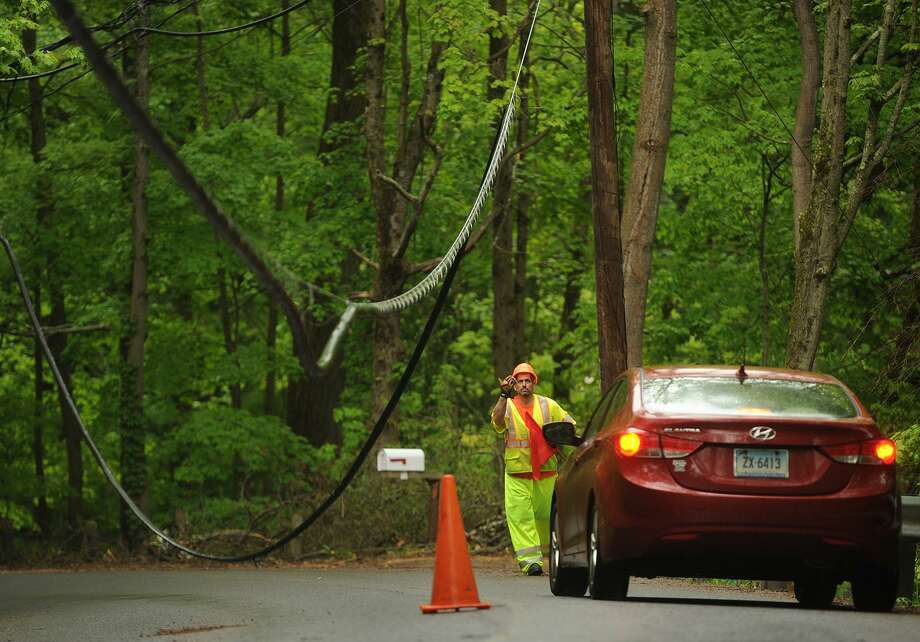 "A utility worker guides cars beneath low hanging power lines on Park Road in Oxford, Conn. on Tuesday, May 22, 2018. First Selectman George Temple called the May 15th storm that knocked out power to the town ""the worst natural disaster"" in the town's history. Photo: Brian A. Pounds / Hearst Connecticut Media / Connecticut Post"